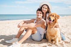 Couples dans l'amour jouant avec leur chien sur la plage Photographie stock libre de droits