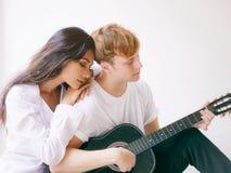 Couples dans l'amour jouant la guitare acoustique Photographie stock libre de droits