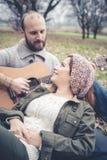 Couples dans l'amour jouant la sérénade avec la guitare Image stock