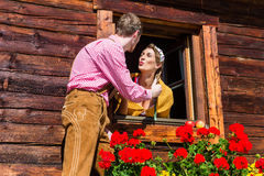 Couples dans l'amour à la fenêtre de hutte de montagne Photographie stock