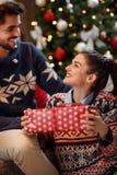 Couples dans l'amour la nuit de Noël partageant des cadeaux Images libres de droits