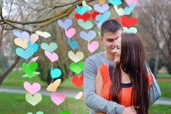 Couples dans l'amour la Saint-Valentin en parc avec des coeurs Image stock