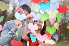 Couples dans l'amour la Saint-Valentin en parc avec des coeurs Images stock