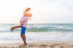Couples dans l'amour Le jeune homme asiatique de sourire tient l'amie dans des ses bras sur la plage le temps de soirée Images stock