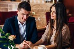 Couples dans l'amour dans le restaurant tenant des mains Photos libres de droits