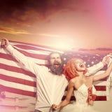 Couples dans l'amour Les couples heureux tiennent le drapeau américain Photographie stock