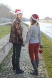 Couples dans l'amour marchant dehors avec des chapeaux de Noël Images libres de droits