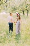 Couples dans l'amour marchant dehors tenant les mains, le jeune homme attirant et la guirlande de port de femme la date, regardan Photographie stock libre de droits