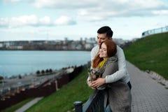 Couples dans l'amour marchant le long du bord de mer avec son chien Photos libres de droits