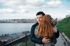 Couples dans l'amour marchant le long du bord de mer avec son chien Photo stock