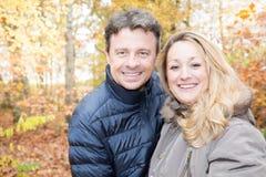 Couples dans l'amour marchant par un parc un jour ensoleillé d'automne Images libres de droits