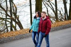 Couples dans l'amour marchant sur la route à un jour merveilleux d'automne Images stock