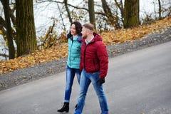 Couples dans l'amour marchant sur la route à un jour merveilleux d'automne Image stock