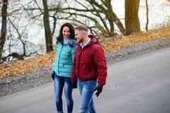 Couples dans l'amour marchant sur la route à un jour merveilleux d'automne Photographie stock