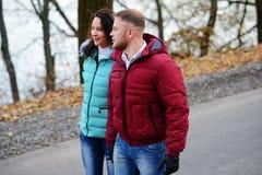 Couples dans l'amour marchant sur la route à un jour merveilleux d'automne Photographie stock libre de droits