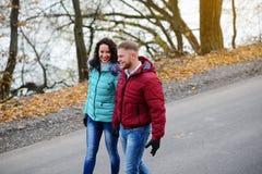 Couples dans l'amour marchant sur la route à un jour merveilleux d'automne Photos stock