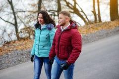 Couples dans l'amour marchant sur la route à un jour merveilleux d'automne Image libre de droits