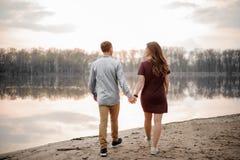 Couples dans l'amour marchant sur un sable humide le long du bord de lac sur le fond des arbres Images stock