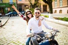 Couples dans l'amour montant une motocyclette Jeunes cavaliers s'amusant en voyage Images stock
