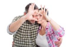 Couples dans l'amour montrant le symbole de coeur Photographie stock