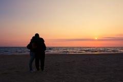 Couples dans l'amour observant le coucher du soleil Photographie stock libre de droits