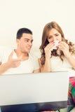 Couples dans l'amour observant le film triste dans le lit sur l'ordinateur portable Image stock