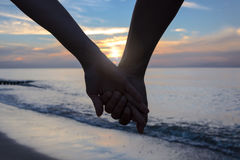 Couples dans l'amour par la mer au coucher du soleil image stock