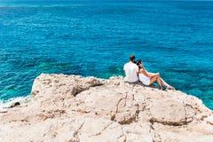 Couples dans l'amour par la mer sur la roche Images libres de droits