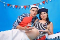 Couples dans l'amour pendant la grossesse dans un type marin Photos libres de droits