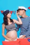Couples dans l'amour pendant la grossesse dans un type marin Photographie stock libre de droits