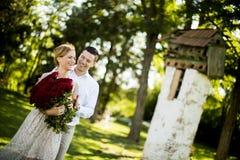 Couples dans l'amour posant dehors avec un bouquet des roses rouges Photo libre de droits