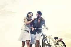 Couples dans l'amour poussant la bicyclette ensemble Photo stock