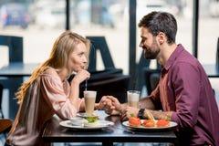 Couples dans l'amour prenant le déjeuner ensemble dans le restaurant Image libre de droits