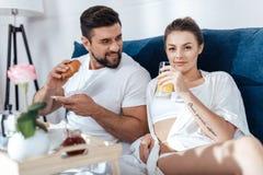 Couples dans l'amour prenant le petit déjeuner dans le lit Photo libre de droits