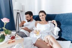 Couples dans l'amour prenant le petit déjeuner dans le lit Photographie stock