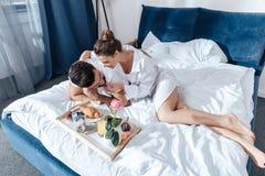 Couples dans l'amour prenant le petit déjeuner dans le lit Photos libres de droits