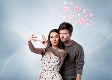 Couples dans l'amour prenant le selfie avec le coeur rouge Photos stock