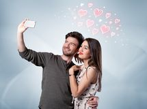 Couples dans l'amour prenant le selfie avec le coeur rouge Photos libres de droits