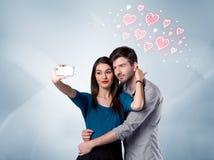 Couples dans l'amour prenant le selfie avec le coeur rouge Images libres de droits