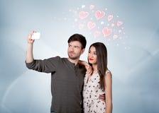 Couples dans l'amour prenant le selfie avec le coeur rouge Image stock
