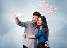 Couples dans l'amour prenant le selfie avec le coeur rouge Photo stock