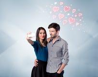 Couples dans l'amour prenant le selfie avec le coeur rouge Images stock