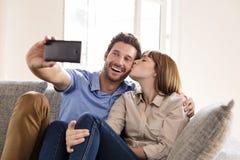Couples dans l'amour prenant un selfie avec un téléphone portable Elle l'embrasse Photo libre de droits