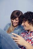 Couples dans l'amour regardant des smartphones et rire Photos libres de droits