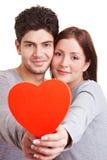Couples dans l'amour retenant le coeur rouge Image stock