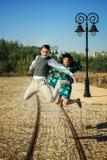 Couples dans l'amour sautant en air haut au milieu de la rue dans l'ol Photo stock