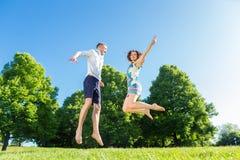 Couples dans l'amour sautant sur le parc Image libre de droits