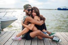 Couples dans l'amour se reposant et embrassant à la jetée de mer en bois Images stock