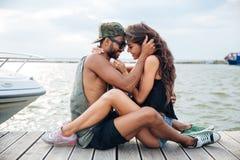 Couples dans l'amour se reposant et embrassant à la jetée de mer en bois Photographie stock libre de droits