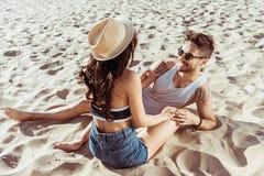 Couples dans l'amour se reposant sur la plage tout en passant le temps ensemble Photographie stock libre de droits